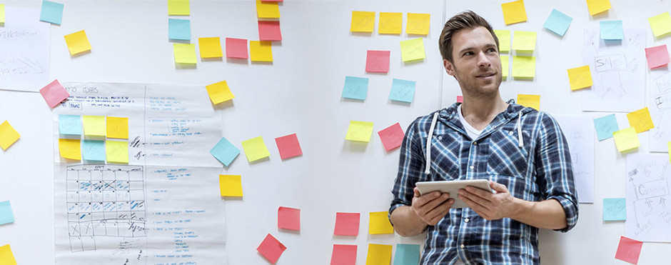UX Designer leaning against a whiteboard with post it notes